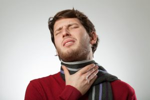 Man in scarf suffering from sore throat